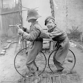 Nigel Henderson: Two unidentified children playing with bicycle wheels