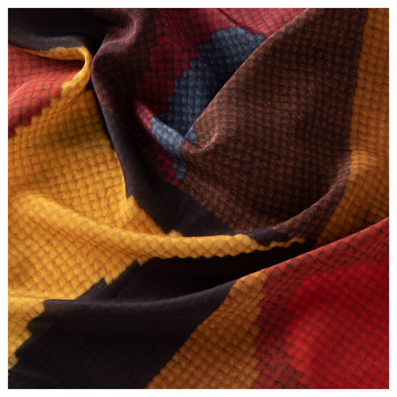 Scrunched detail of a large silk scarf with a print of an embroidered artwork in blues, reds, browns and yellows.