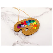 Wooden paint pallete necklace with paint splotches on marble background