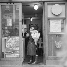 Nigel Henderson: Unidentified boy in a doorway with flowers