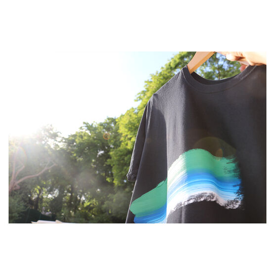 Black t-shirt with blue, green and white stroke against a black t-shirt, against a leafy backdrop