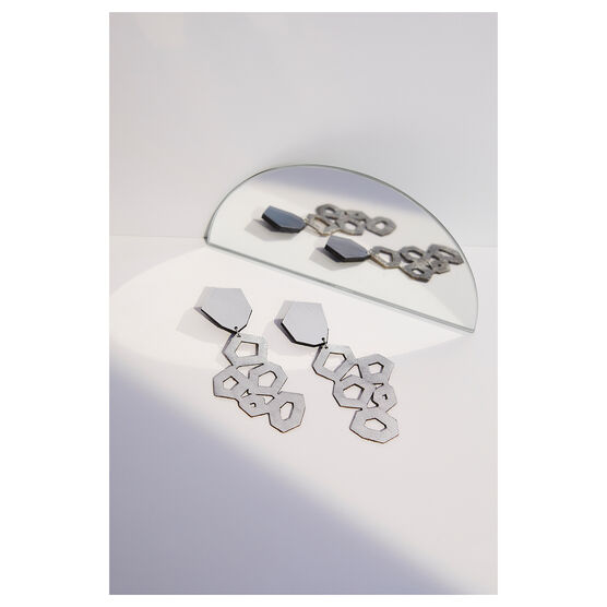 silver leather earrings, laying flat next to a mirror