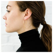 Gold hammered metal earrings in a crescent shape on model