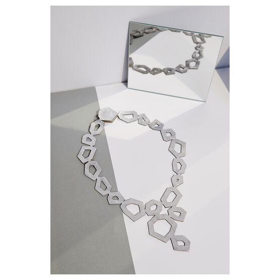 Silver leather necklace laying flat next to a mirror